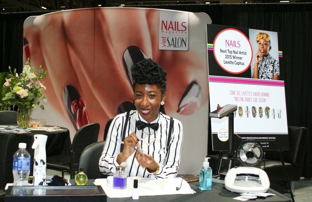 <p>NTNA Season 2 winner Lavette Cephus demos her Rubix Cube nail at the NAILS booth.</p>