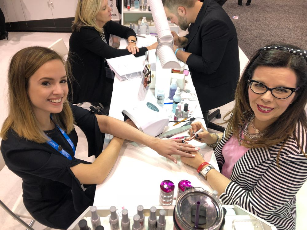 <p>Modern Salon associate editor Mary Kaleta stopped by the Orly booth to get a glitter gradient from Tracy Vinson.</p>