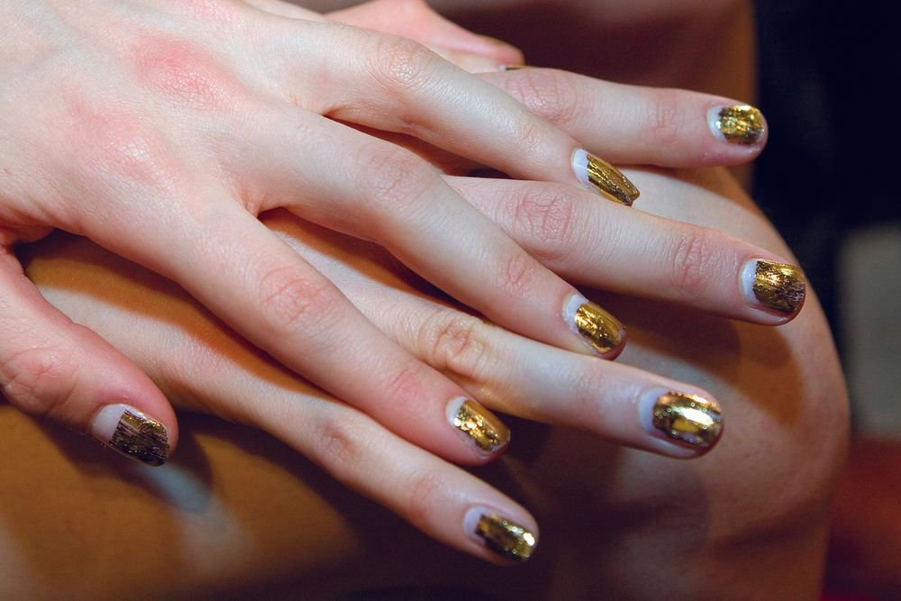 <p>For the Cushnie et Ochs show, the <strong>Dashing Diva</strong> team created nails that looked as if they&rsquo;d been dipped in gold. The nails were painted with a basic clear base coat and then a gold foil was applied by rubbing it straight onto the nail.&nbsp;(Photography by Ann Lawlor)</p>