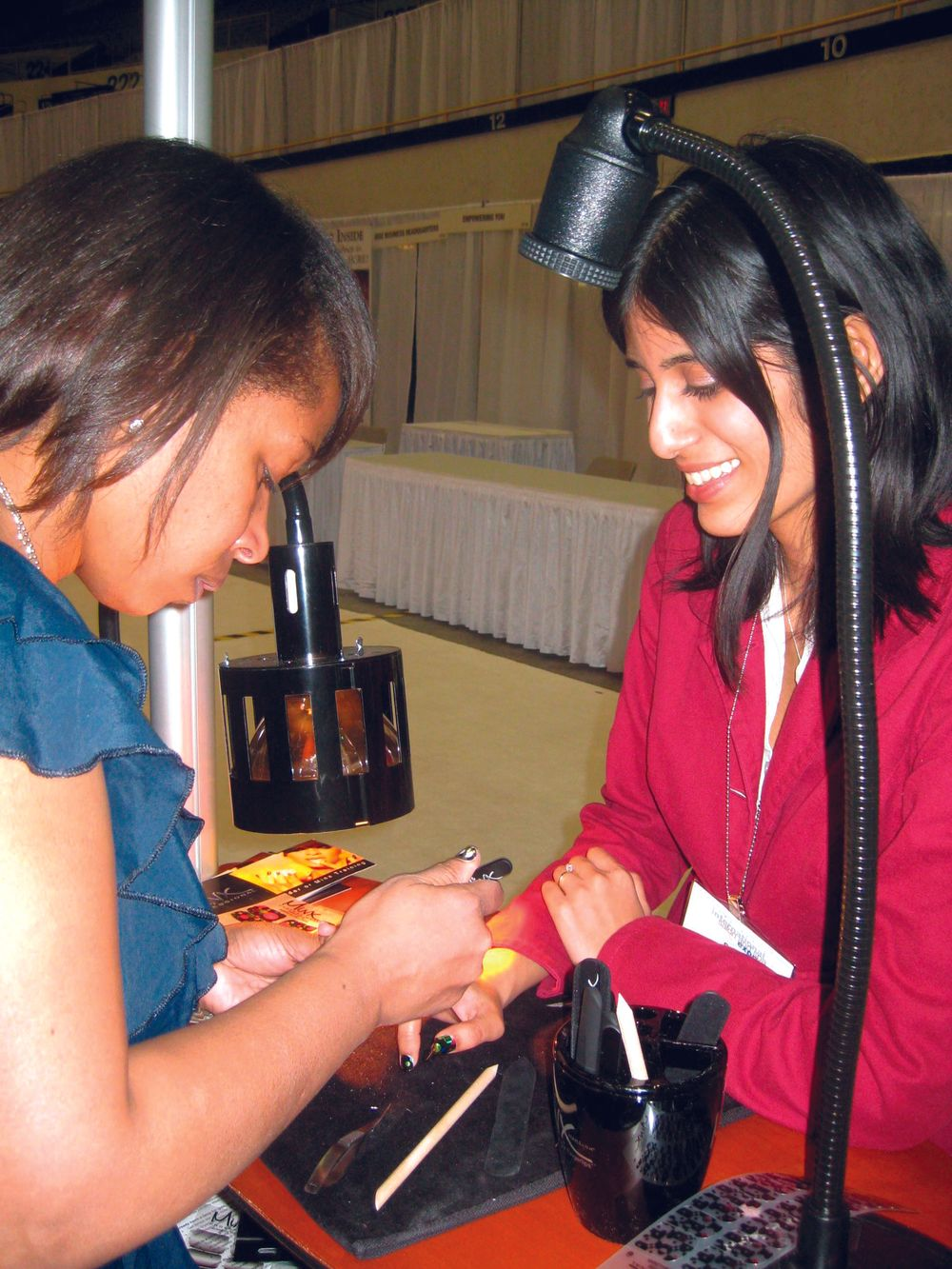 <p>Celebrity nail tech Lisa Logan (left) designed her own line of Minx nail coatings and applied her whimsical Happy Dots pattern to managing editor Sree Roy&rsquo;s fingernails.</p>