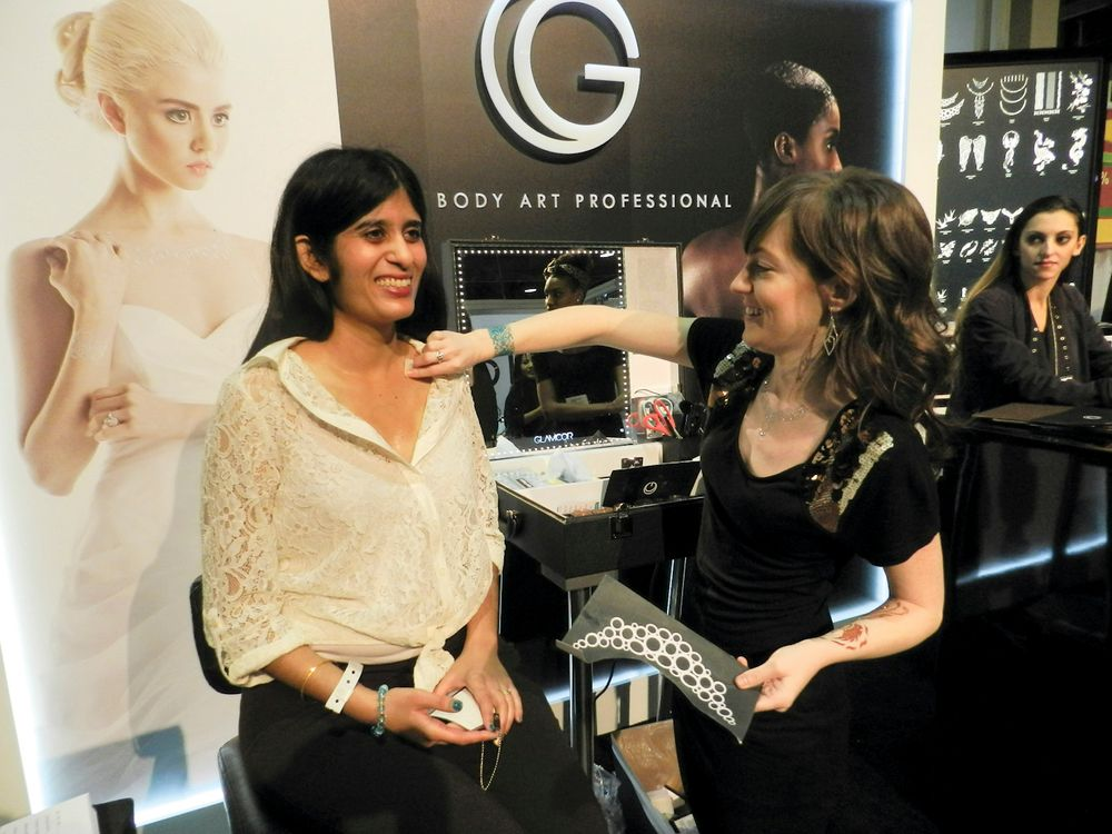 <p>Body art professional Julie Partin cleans NAILS&rsquo; Sree Roy&rsquo;s skin at the G &mdash; The Body Art Professional booth prior to applying a glitter necklace tattoo.</p>
