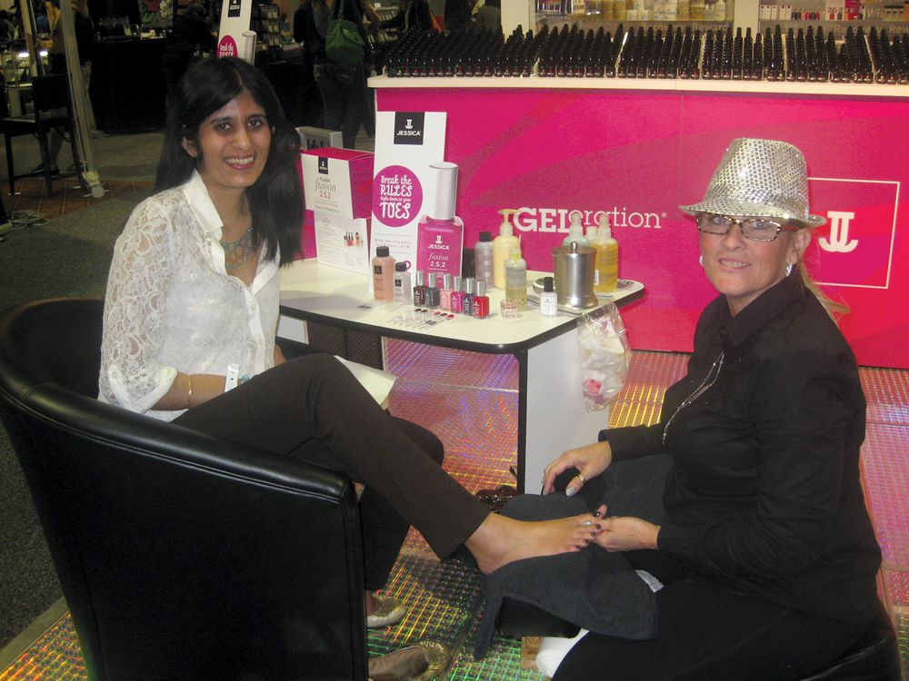 <p>At the Jessica Cosmetics booth, Kandice Astamendi demonstrates the company&rsquo;s new Fusion 2.5.2 product &mdash; a gel-polish that dries in two minutes without a UV light &mdash; on NAILS&rsquo; Sree Roy.</p>
