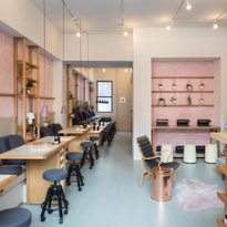 The salon interior hosts an abundance of plants and fresh flowers along the sides of each...