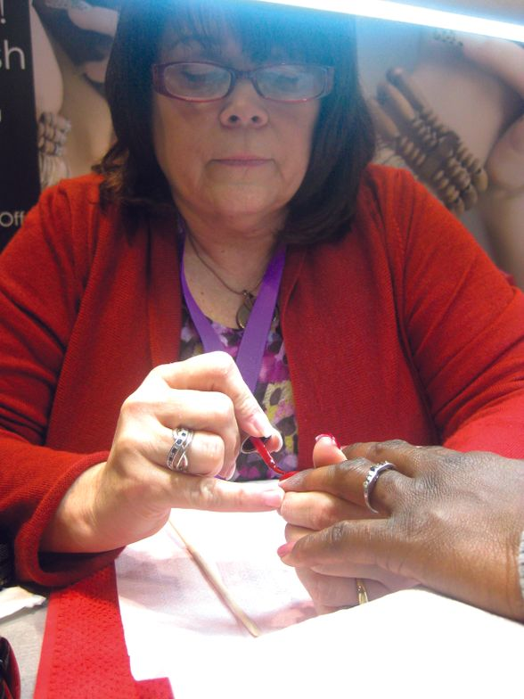 <p>En Vogue launched Lac It!, a gel polish line, which veteran tech Terri Wells demonstrates on an attendee.</p>