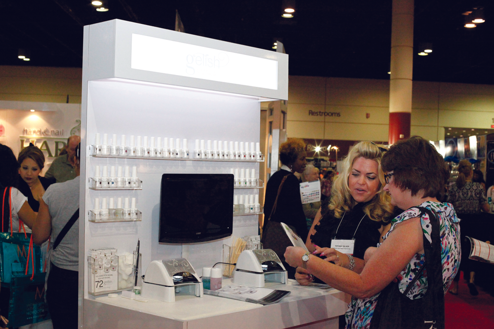 <p>Hand &amp; Nail Harmony&rsquo;s Tiffany Silver gives a show attendee tips and information on using Gelish at one of the Try-Me Stations set up for show attendees.</p>