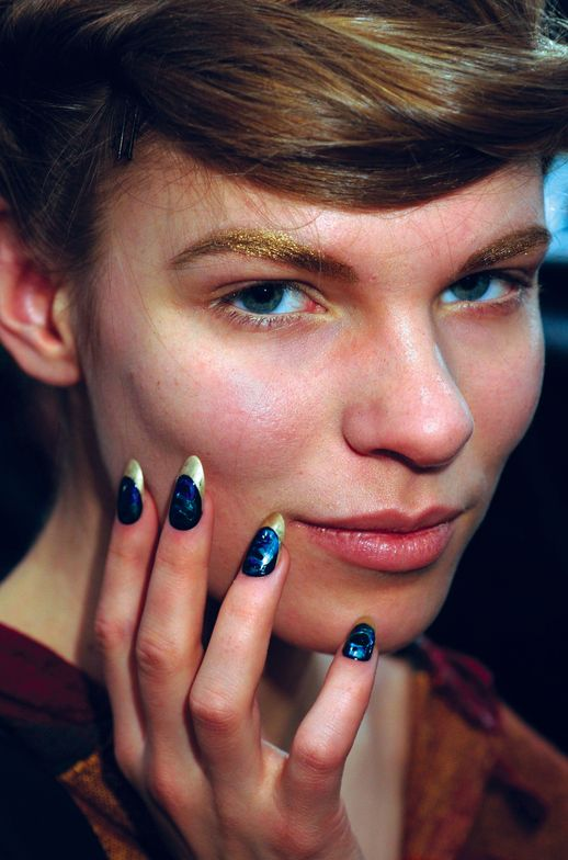 <p>Kristina Estabrooks fashioned rainforest-inspired manicures by <strong>CND</strong> for Jen Kao. She used long, almond-shaped nails based with Gold Chrome and Midnight Sapphire, accented with drops of Gold Pearl, Ice Blue Shimmer, and Midnight Sapphire for a psychedelic stained glass effect. <em>Photography courtesy of Creative Nail Design</em></p>