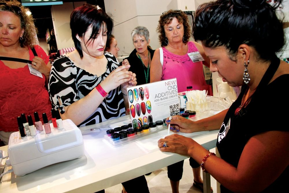<p>CND&rsquo;s Lisa Wong (right) helped show attendee Stephanie Russo try out CND&rsquo;s new pure pigment and effects at the Additives nail bar.<br /><br /></p>
