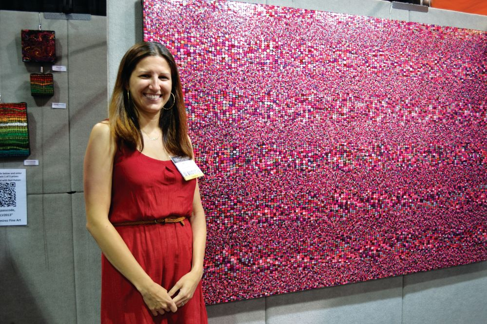 <p>Artist Kelley Ramirez poses against one of her pieces, which took over 300 bottles of nail polish to complete.</p>