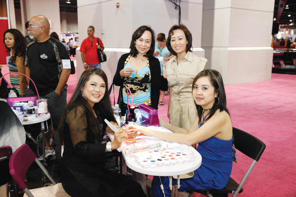 <p>Christrio educator Lee Thai demonstrates glitter gels on attendees Pauline Ong, Holly Ong, and Mai Thao.</p>