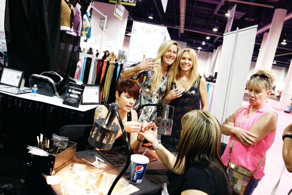 <p>Janice Jordan and Dawn Lynch-Goodwin show off their nails as an attendee gets Minxed by Lisa Delegge.</p>