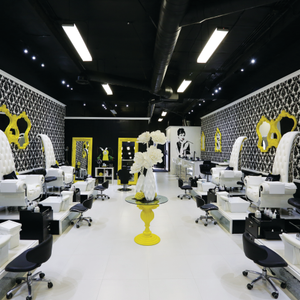 At Laqué's North Hollywood location, bright yellow framed mirrors are offset by white...