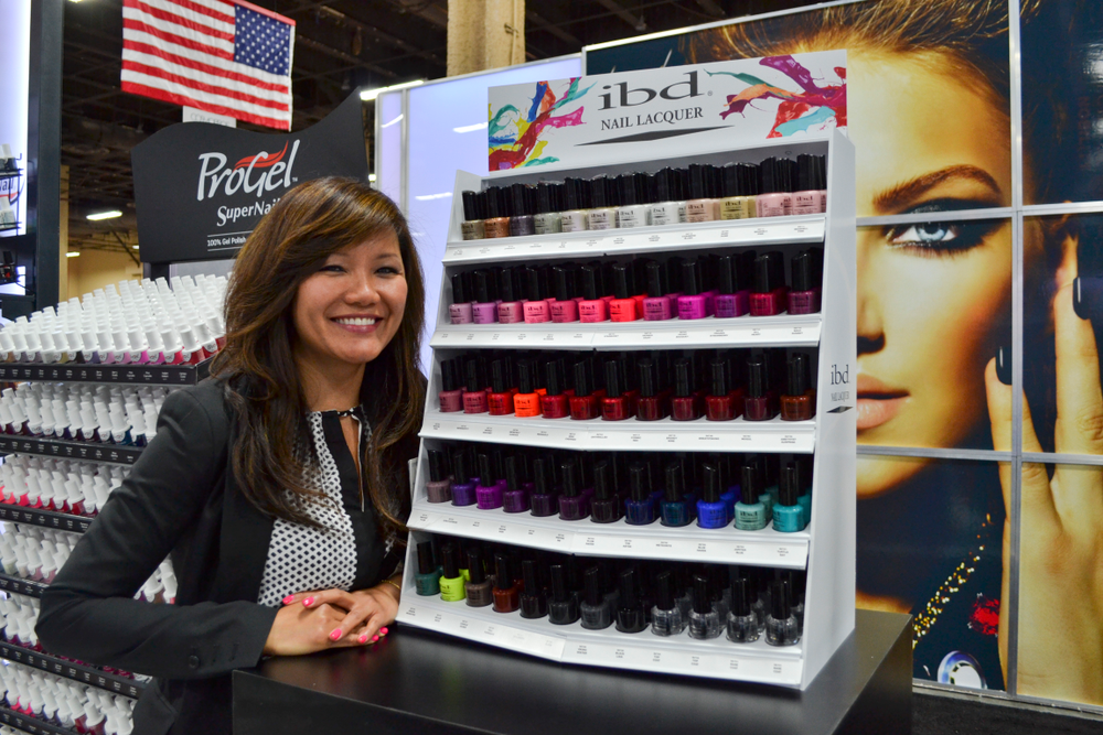 <p>Brand manager Dinh Pham is all smiles next to IBD&rsquo;s lacquer line.</p>