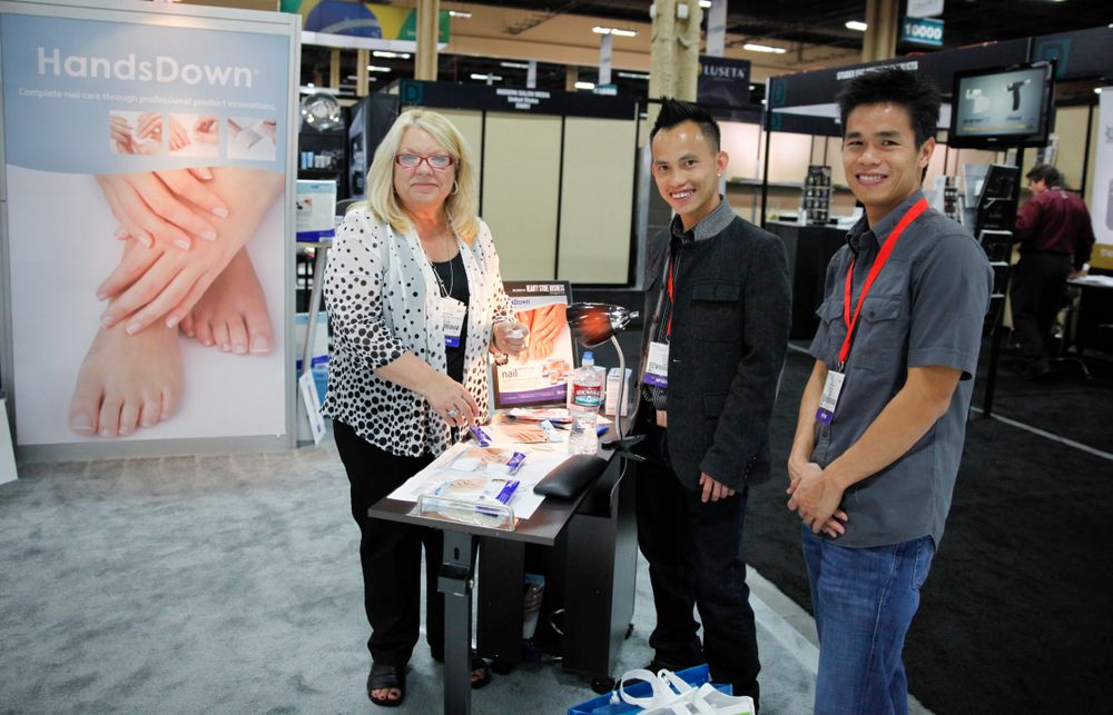 <p>Graham Professional&rsquo;s Debbie Schlise demos the company&rsquo;s HandsDown nail wraps for Nails4Viet.com&rsquo;s Henry Duong and Bao Nguyen.</p>