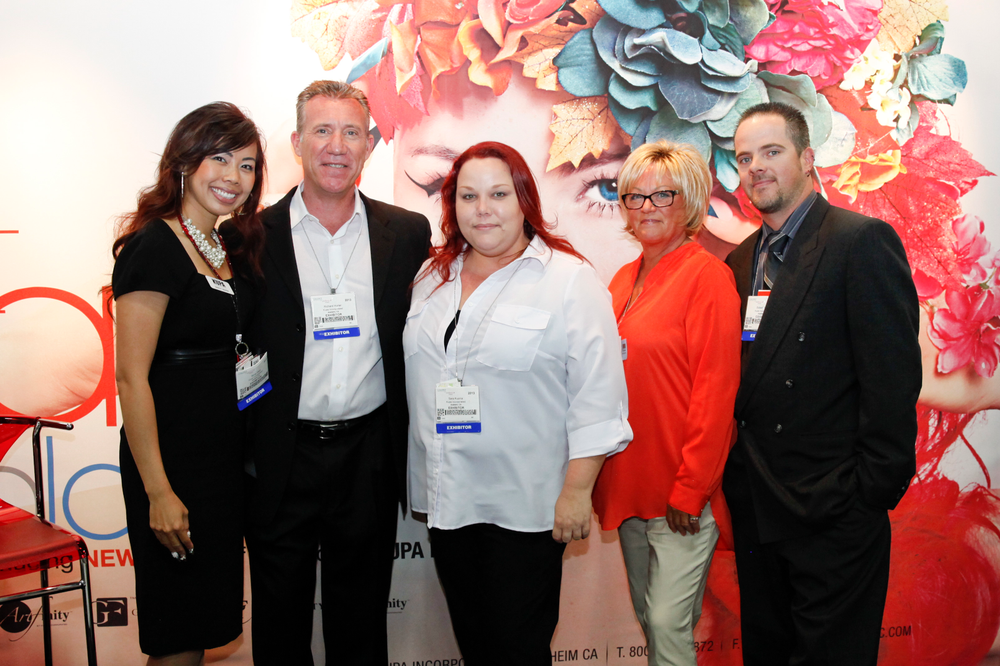 <p>The Kupa Team pose in front of their colorful new booth, from left to right: Sindy Mark, Richard Hurter, Sarah Kuzma, Vicki Peters, and Robert Arthur.</p>