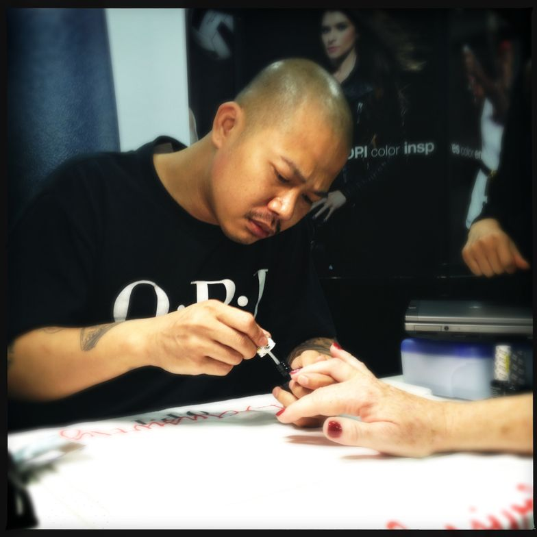 <p>OPI guest artist Vu Nguyen demonstates his nail art expertise on NAILS Magazine's Cyndy Drummey.</p>