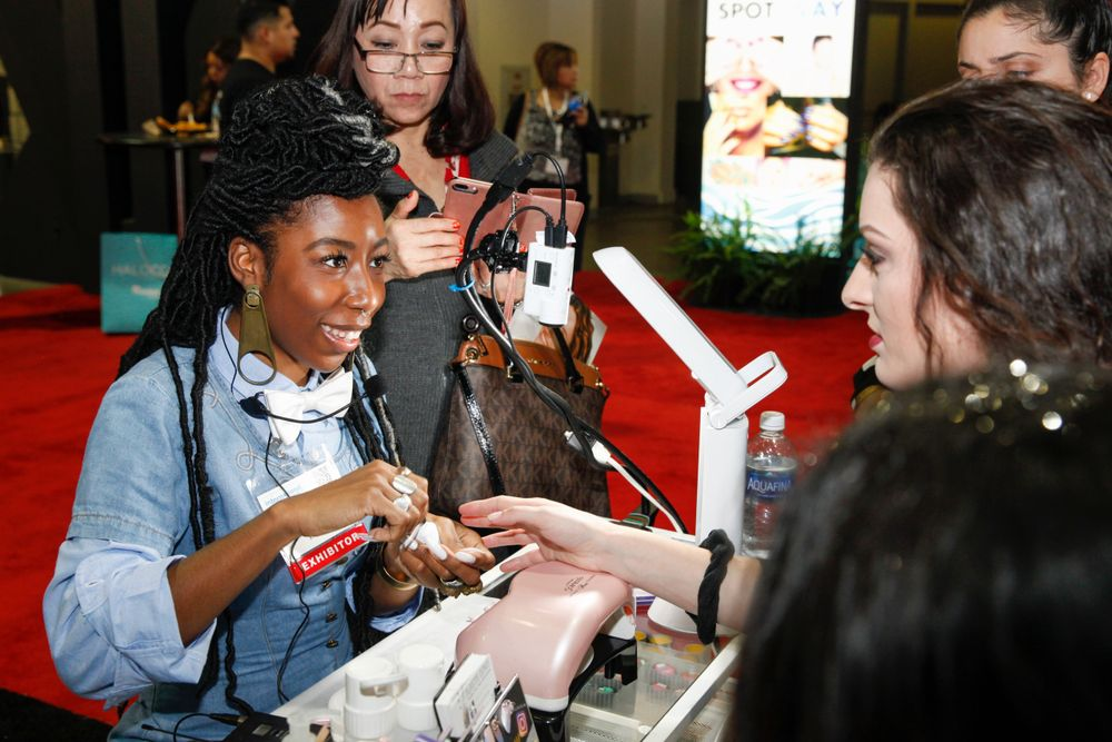 <p>Lavette Cephus demonstrates some designs at the Nail Labo booth.</p>