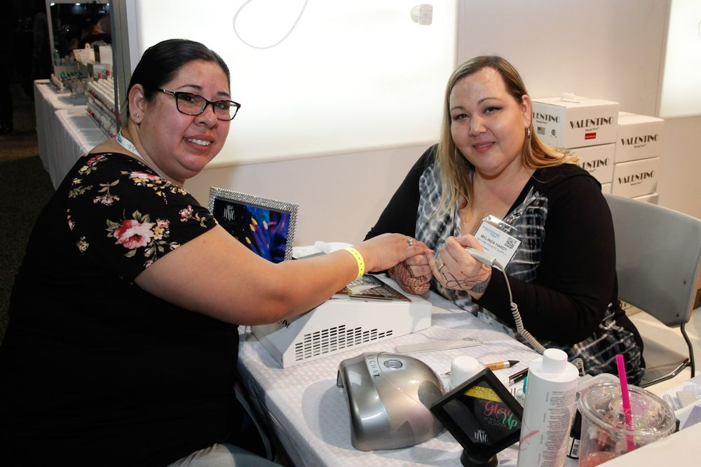 <p>Lupa Rivera gets a demo from Mindy Hardy at Skyline Beauty Supply's booth.</p>