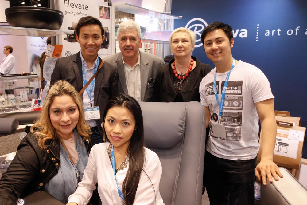 <p>Belava's Vladimir and Natalie Zolotnik (back, center) with salon owners Tuan Vu, Thien Van, Vanessa Santiago, and Trina Truong around the Embrace pedicure chair.</p>
