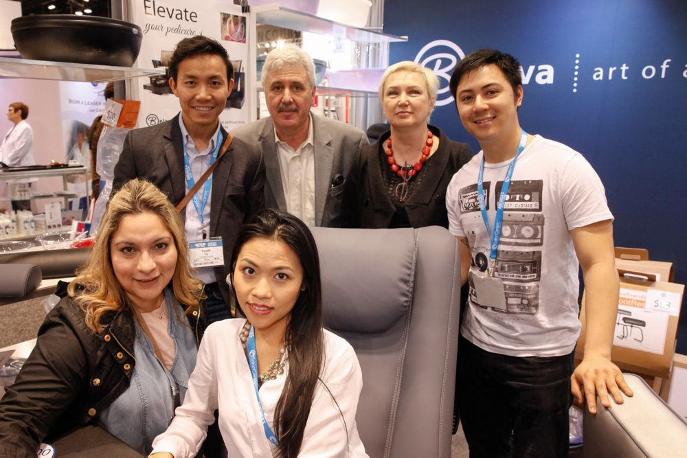 <p>Belava's Vladimir and Natalie Zolotnik (back, center) with salon owners Tuan Vu, Thien Van, Vanessa Santiago, and Trina Truong around the Embrace pedicure chair.</p>