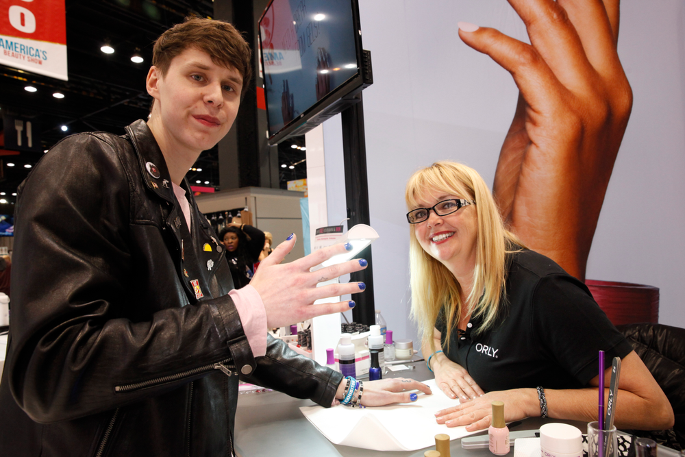 """<p>What happens when a DJ (<a href=""""https://www.instagram.com/shanecanfield/"""">@shanecanfield</a>) spins across from the Orly booth? He gets his nails polished by educator Carla Collier using Orly's new Coastal Crush polish collection.</p>"""