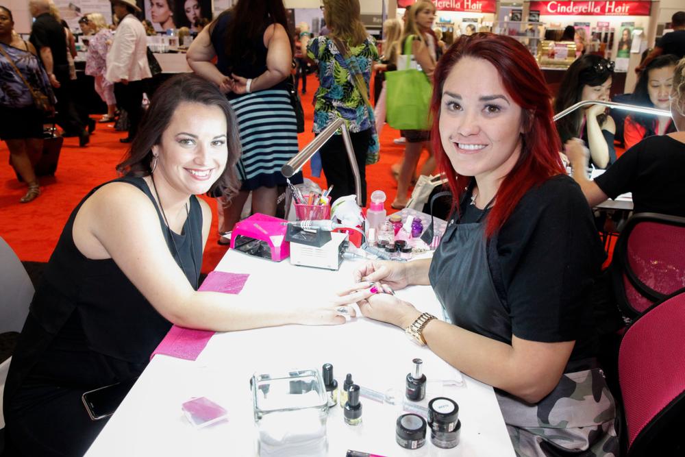 <p>Elegant Glass' Jennifer Garcia (right) does a demo on Juanita Centeno</p>