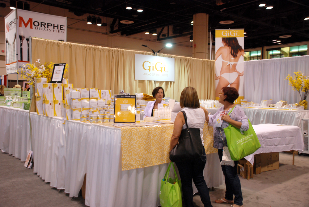 <p>Attendees check out Gigi's waxing and paraffin products at their sunny booth.</p>