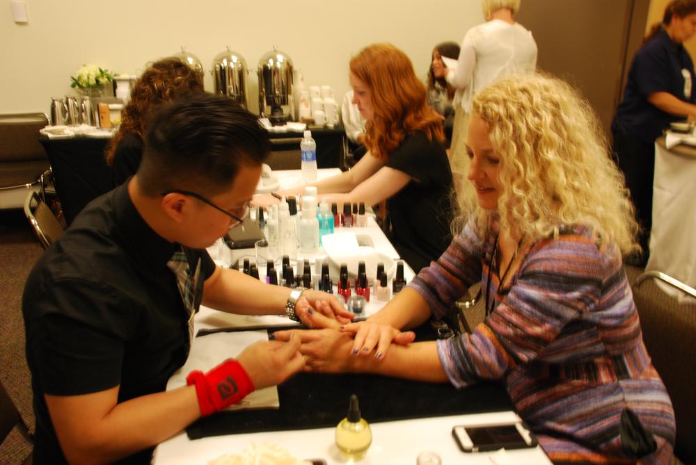 <p>CND nail designer and educator John Nguyen works on NAILS editor Erika Kotite.</p>