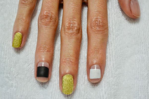 <p>1. After applying base coat to each finger, apply one coat of gold glitter to the pinky and middle finger. Place a wide stripe of black to the ring finger and white to the index. Polish half the thumb nail white, and the other half black.</p>