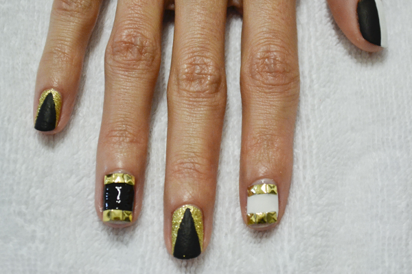 <p>2. Add a triangle of black to the glitter nails. Slick on a layer of top coat and place three square flatback studs to the open space on the ring and index finger.</p>