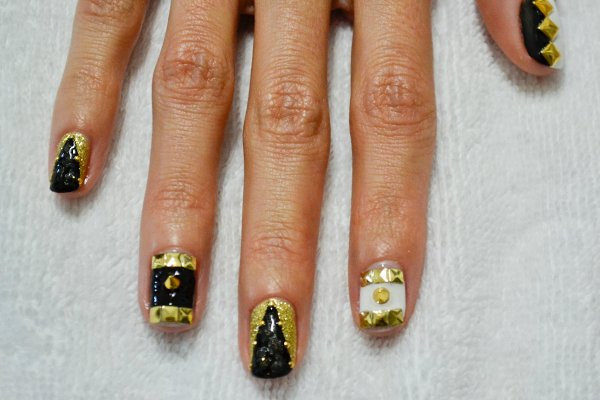 <p>3. Apply top coat to the pinky and middle fingers. Place small metal gold dots along the outside of the black triangle. Once dry, paint on a tiny leopard print in matte top coat over just the black area. Apply top coat to the index and ring fingers, and place one gold spike in the center of the black or white space. Apply top coat over the thumb and place three square flatback studs on the diamond, along the area where the black and white meet.</p>