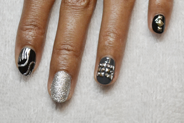 <p>2. Use a fine tipped brush dipped in silver polish to paint abstract wings on the index finger. Topcoat the gray fingernail and apply a checkerboard of small square and circular flatback studs. Apply two smaller square studs and one larger sized stud to the pinky nail.</p>