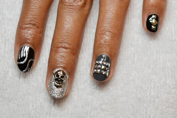 <p>3. Apply one coat of topcoat to the silver glitter fingernail and attach the large skull embellishment. Once dry, apply more top coat around the sides and inside the eyes to affix it in place.</p>