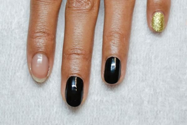 <p>1. Polish the middle and ring fingers black, while the pinky nails and thumbs get polished with gold glitter. Leave the index finger naked.</p>