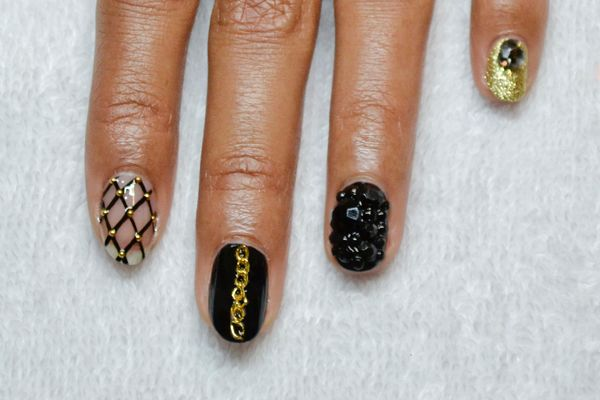 <p>3. Apply top coat to each nail, and apply the embellishments to each. Place small metal dots to the intersections on the fishnet nail. Place a small piece of chain link on the middle finger. Pull back and forth on the chain links to encapsulate it in the topcoat. Mix together multiple sizes of black rhinestones and place onto the nail until covered. Add a trio Swarovski crystals to the pinky to create a cluster.</p>