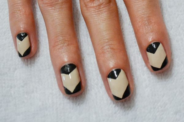 <p>2. Use a fine-tipped paintbrush and black to create a triangle at the base of each fingernail. Repeat the same triangle shape at the tip of each nail.</p>