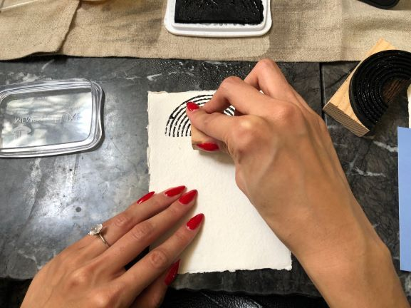 <p>At each seat, a box of handcarved block stamps and a pad of ink was supplied, so everyone had the opportunity to try their hand at creating their own designs.&nbsp;</p>