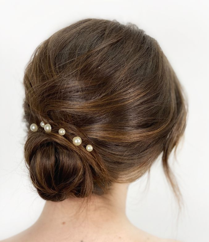 <p>A classic chignon with lots of texture and pearl adornments will be a huge trend this year in bridal, predicts Alders. She installed a row of weft extensions to add density to the bridal style. Hair: @emily.alders</p>