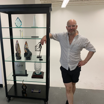 Charlie Price next to his awards display at his Beauty Underground Salon/Studio in Denver,...