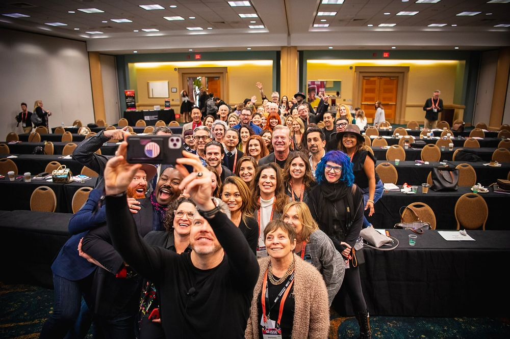 <p>Eric Taylor organizes some of the attendees for a group selfie.</p>