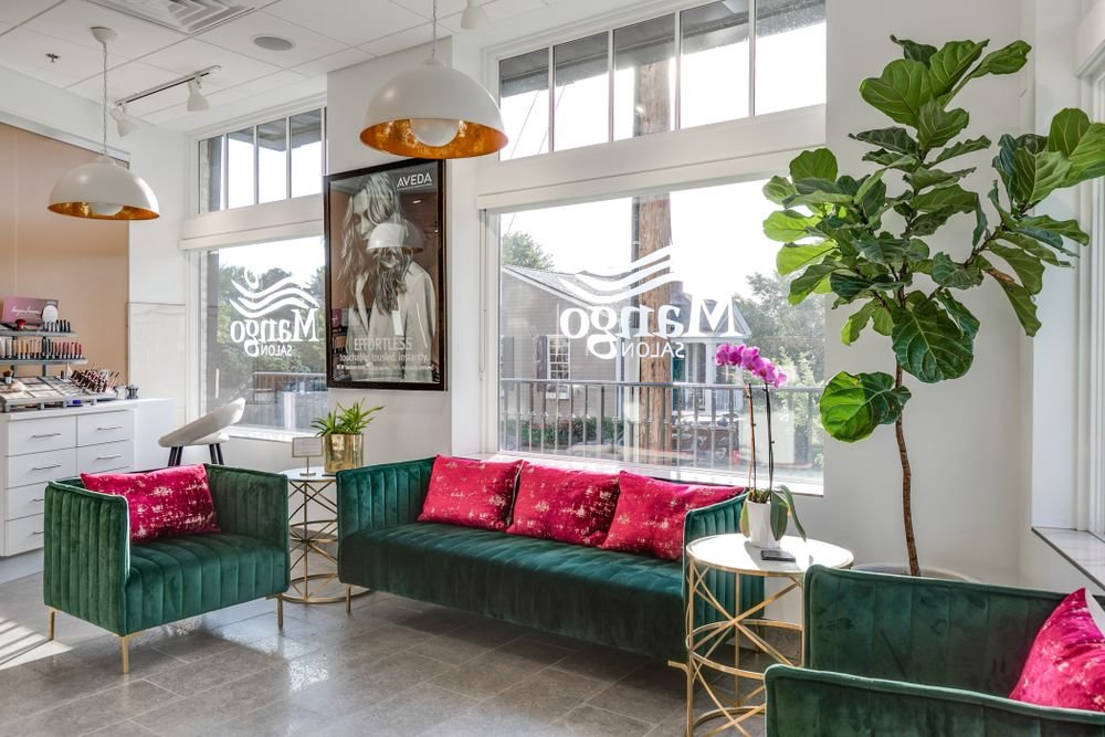 <p>Forest green furnishings with hot pink pillows offer a fun pop of color at Mango Salon in Richmond, Virginia.&nbsp;</p>