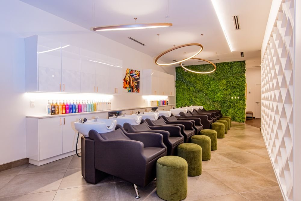 <p>Bright product bottles, a piece of art and a living wall color the shampoo area of Define Hair in Ellicott City, Maryland.</p>