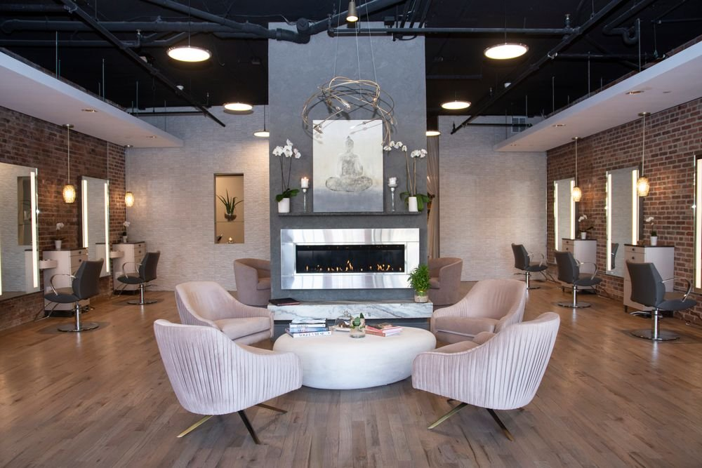 <p>A pastel palette, including champagne pink chairs, invites clients to relax&nbsp;around an elegant fireplace at Karen Joseph Salon in Red Bank, New Jersey.&nbsp;</p>