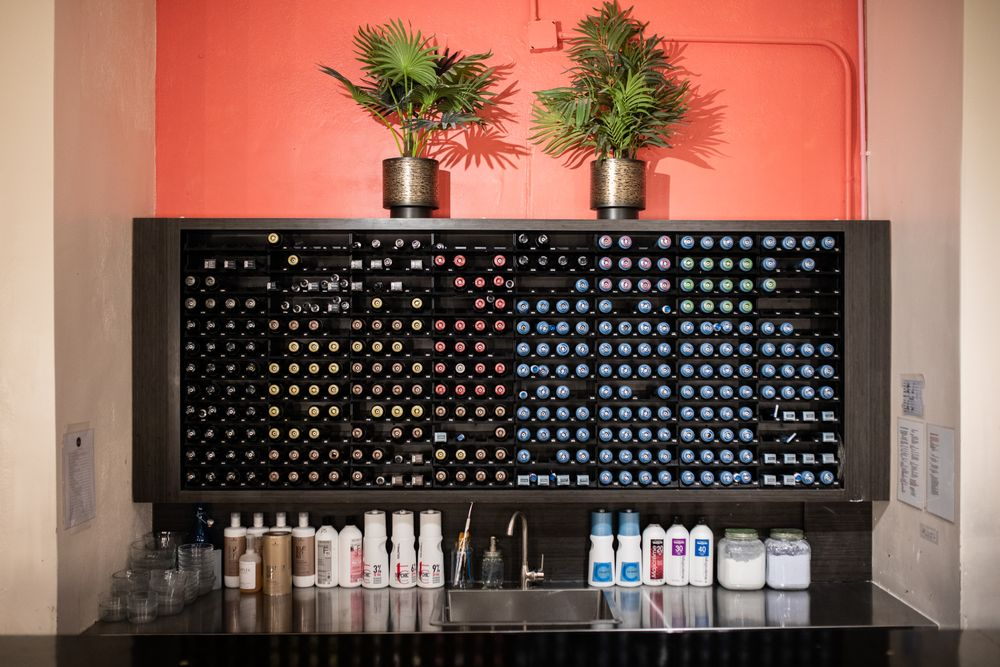 <p>The color area acts as an accent wall with a pop of color and easily organized shelving for the color tubes. The bar is the ultimate come-and-go access so that the stylists can get back to clients faster.</p>