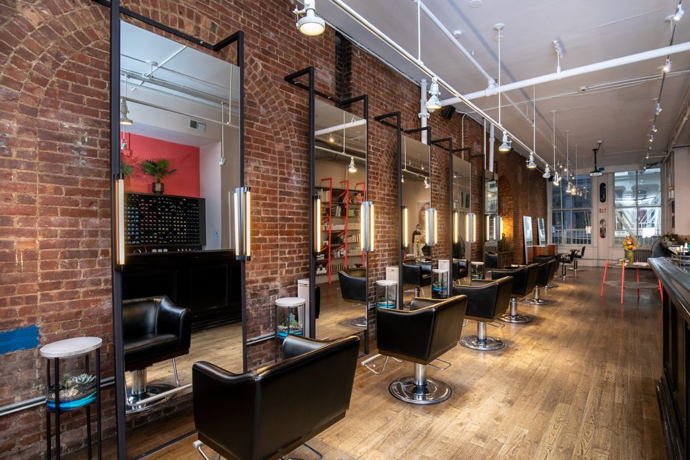 <p>A complete eye line from one end of the salon to the other creates a comfortable and familiar atmosphere, and the&nbsp;view out the Greene Street-facing window is quintessential SoHo. Ott&nbsp;hand-crafted the sand art terrarium side tables, providing pops of teal that complement the oranges and browns in the space.</p>