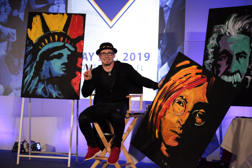 <p>Erik Wahl with the paintings he did live&nbsp;on stage at the ISBN conference. Proceeds from the auction of the program will help launch the debt payback program.&nbsp;</p>