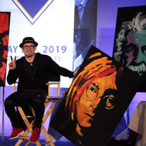 Erik Wahl with the paintings he did live on stage at the ISBN conference. Proceeds from the...