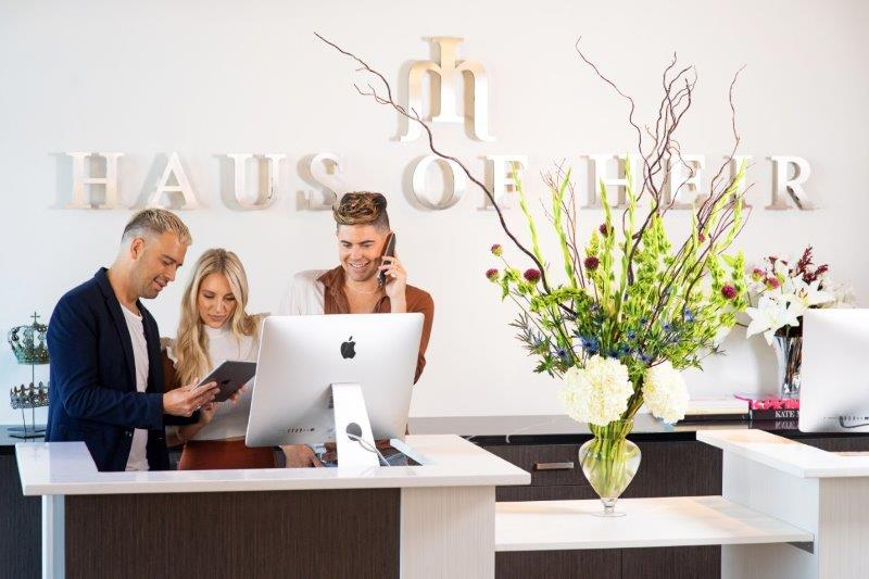 Owners Ramiro Corrales, Taylor Miller and Cameron Kepford check out a client's recent positive review at Haus of Heir in Davenport, Iowa.  - Karen Bishop