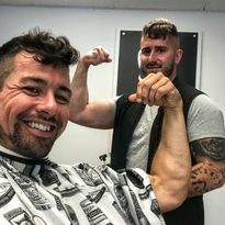 Shawn Wiley and his barber Johnny Marciano celebrate his new hair growth.