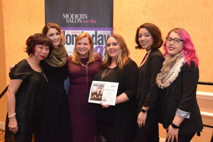 The team from Karen Allen Salon and Spa in Riverside, CA, accepting one of their previous ST200 honors at Serious Business. 