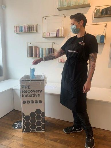 A stylist safely disposes of a client's used mask, as part of Green Circle Salon's  PPE Recovery Initiative.   -